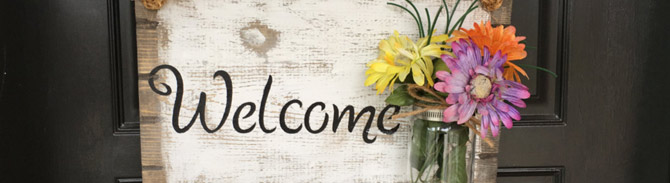 Wooden door sign that reads welcome with bouquet of flowers