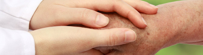 Close up of a caregiver holding an elderly person's hand