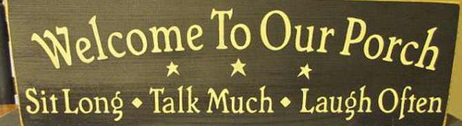 Wooden sign that reads welcome to our porch, sit long, talk much, laugh often