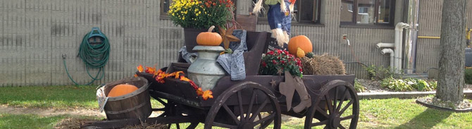 Exterior of hospital featuring a fall wagon with pumpkins, flowers and scarecrow